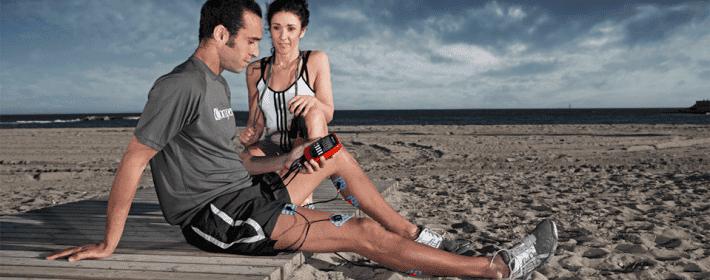 Pareja empleando electroestimulador en la playa
