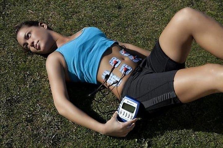 Chica tumbada usando electroestimulador