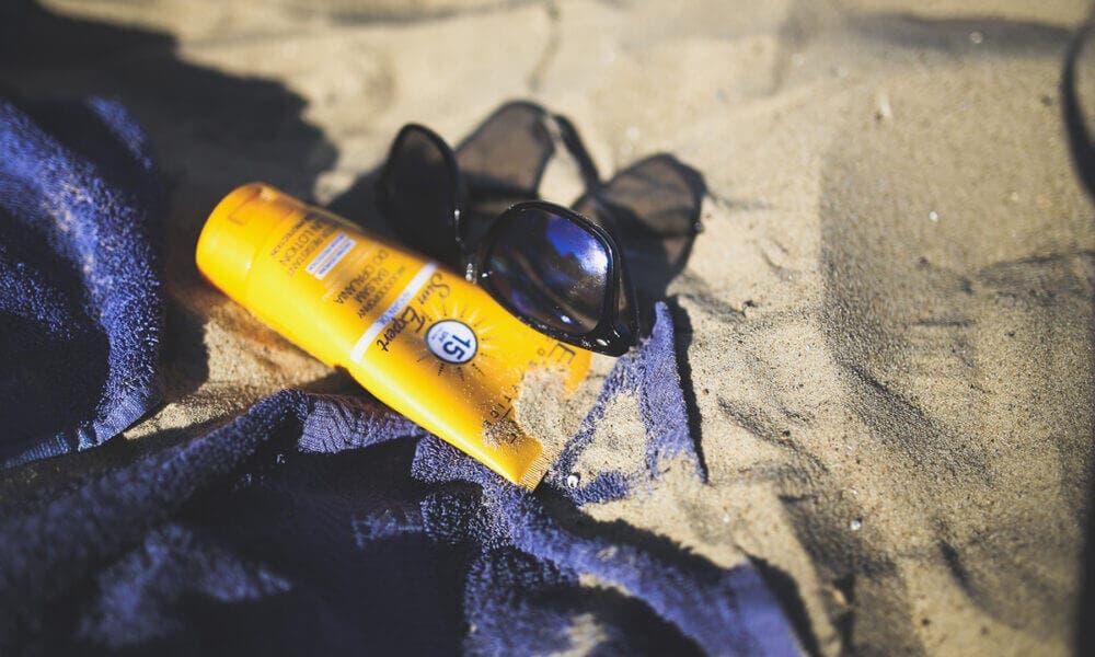 crema y gafas de sol
